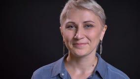 Close-upspruit van volwassen aantrekkelijk Kaukasisch vrouwelijk gezicht met kort blondehaar die cheerfully en camera glimlachen  stock fotografie