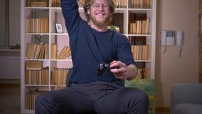 Close-upspruit van volwassen aantrekkelijke mannelijke het spelen videospelletjes met opwinding in de comfortabele flat binnen stock videobeelden