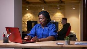 Close-upspruit van volwassen Afrikaanse Amerikaanse onderneemster gebruikend laptop en zijnd gelukkig het vieren succes in het bu stock videobeelden
