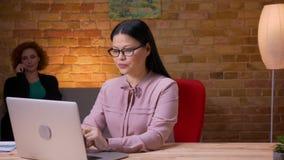 Close-upspruit van volwassen Aziatische onderneemster die aan laptop werken die een telefoongesprek hebben en binnen in het burea stock video