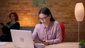 Close-upspruit van volwassen Aziatische onderneemster die online op laptop binnen in het bureau winkelen Het vrouwelijke werkneme stock footage