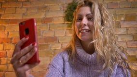 Close-upspruit van volwassen Kaukasisch aantrekkelijk wijfje die een videogesprek op de telefoon hebben en hello cheerfully het g stock videobeelden