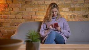 Close-upspruit van volwassen Kaukasisch blondewijfje die de telefoon met behulp van terwijl het zitten op de laag binnen bij comf stock video