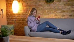 Close-upspruit van volwassen Kaukasisch blondewijfje die de telefoon met behulp van terwijl het zitten op de laidback laag uitspr stock footage