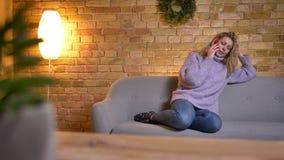 Close-upspruit van volwassen Kaukasisch blondewijfje die een toevallig gesprek op de telefoon hebben terwijl het zitten op de laa stock footage