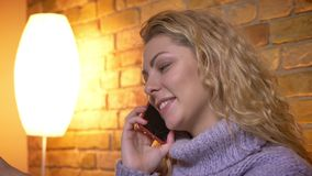 Close-upspruit van volwassen Kaukasisch blondewijfje die een toevallig gesprek op de telefoon hebben terwijl het zitten op de laa stock videobeelden