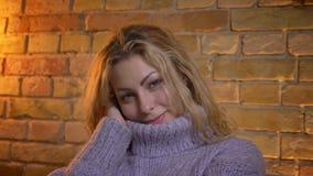 Close-upspruit van volwassen Kaukasisch blondewijfje die haar leuk gezicht in een warme sweater verbergen en camera met vreugde b stock video