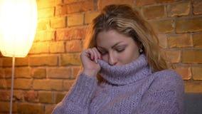 Close-upspruit van volwassen Kaukasisch blondewijfje die haar leuk gezicht in een warme sweater verbergen terwijl binnen het zitt stock footage