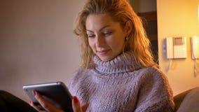 Close-upspruit van volwassen Kaukasisch blondewijfje die op de tablet doorbladeren en cheerfully binnen in een comfortabele flat  stock videobeelden