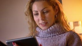 Close-upspruit van volwassen Kaukasisch blondewijfje die op de tablet doorbladeren en pret hebben die gelukkig binnen in comforta stock footage