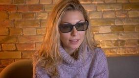 Close-upspruit van volwassen Kaukasisch blondewijfje die op een 3D film op TV in 3D glazen letten en pret hebben terwijl het zitt stock footage