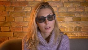 Close-upspruit van volwassen Kaukasisch blondewijfje die op een 3D film op TV in 3D glazen met nieuwsgierige gezichts letten stock videobeelden
