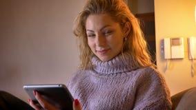 Close-upspruit van volwassen Kaukasisch blondewijfje die op tablet en cheerfully het glimlachen binnen het bekijken camera doorbl stock video