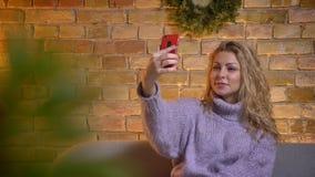 Close-upspruit van volwassen Kaukasisch blondewijfje die selfies op de telefoon nemen terwijl het zitten op de laag binnen bij co stock videobeelden