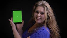 Close-upspruit van volwassen Kaukasisch wijfje gebruikend de tablet en tonend het groene scherm aan camera die met opwinding glim stock videobeelden