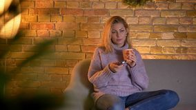 Close-upspruit van volwassen Kaukasische blonde vrouwelijke het letten op TV die een kop van warme thee houden terwijl binnen het stock video