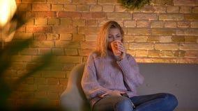 Close-upspruit van volwassen Kaukasische blonde vrouwelijke het letten op TV die een kop van warme thee houden terwijl het zitten stock video