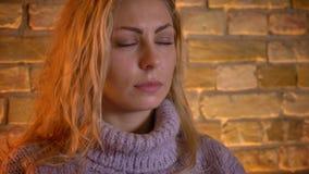 Close-upspruit van volwassen Kaukasische blonde vrouwelijke het letten op TV met geinteresseerde gelaatsuitdrukking die een kop v stock videobeelden