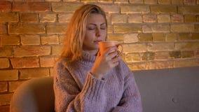 Close-upspruit van volwassen Kaukasische blonde vrouwelijke het letten op TV met nieuwsgierige gelaatsuitdrukking die een kop van stock videobeelden