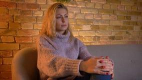 Close-upspruit van volwassen Kaukasische blonde vrouwelijke het letten op TV met nieuwsgierige gelaatsuitdrukking en het gebruike stock video