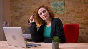 Close-upspruit van volwassen Kaukasische onderneemster die aan laptop binnen in het bureau werken Zakenman die haar behandelen stock video