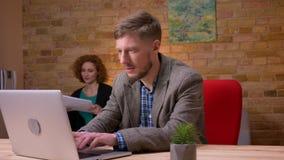 Close-upspruit van volwassen Kaukasische zakenman die aan laptop binnen in het bureau werken Onderneemster die hem behandelen stock videobeelden
