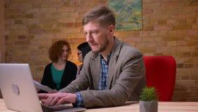 Close-upspruit van volwassen Kaukasische zakenman die aan laptop binnen in het bureau werken Twee vrouwelijke werknemers behandel stock videobeelden