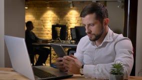 Close-upspruit van volwassen Kaukasische zakenman die de tablet voor laptop binnen in het bureau gebruiken stock afbeeldingen