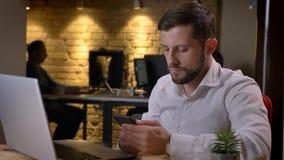 Close-upspruit van volwassen Kaukasische zakenman die de telefoon voor laptop binnen in het bureau met behulp van royalty-vrije stock afbeeldingen