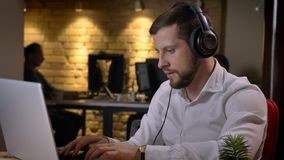 Close-upspruit van volwassen Kaukasische zakenman die in hoofdtelefoons aan muziek luisteren terwijl het typen op laptop binnen i royalty-vrije stock afbeeldingen