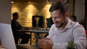 Close-upspruit van volwassen Kaukasische zakenman gebruikend de telefoon voor laptop en binnen cheerfully glimlachend binnen stock foto