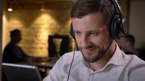 Close-upspruit van volwassen Kaukasische zakenman in hoofdtelefoons die op de tablet texting en cheerfully op de werkplaats gliml stock afbeeldingen