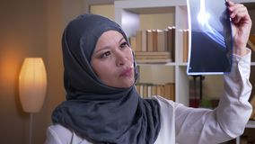 Close-upspruit van volwassen moslim vrouwelijke arts in hijab die gelukkig een röntgenstraal in de bibliotheek binnen onderzoeken stock videobeelden
