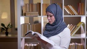 Close-upspruit van volwassen moslim vrouwelijke student die in hijab een boek lezen een medisch onderwijs krijgen die zich bevind stock video