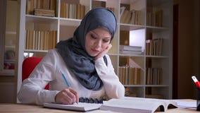 Close-upspruit van volwassen moslim vrouwelijke student in hijab die een medisch onderwijs krijgen bestuderend voor een medisch e stock footage