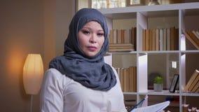 Close-upspruit van volwassen moslimonderneemster die de grafiek in de bibliotheek bestuderen die nadenkend en camera bekijken zij stock footage