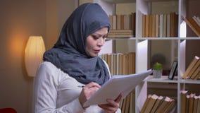 Close-upspruit van volwassen moslimonderneemster die de grafiek in de bibliotheek op de werkplaats binnen bestuderen stock video