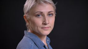 Close-upspruit van volwassen vrij Kaukasisch vrouwelijk gezicht met kort blondehaar die en camera met achtergrond draaien bekijke royalty-vrije stock afbeelding