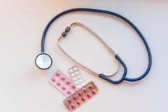 Close-upstethoscoop dichtbij capsules in blaarpak op witte lijst Hoogste mening Drug en pillen met phonendoscope gezondheid royalty-vrije stock foto's