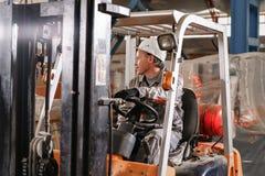 Close-upstuurwiel en hefbomen Mens die een vorkheftruck drijven door een pakhuis in een fabriek bestuurder in eenvormig en stock afbeeldingen