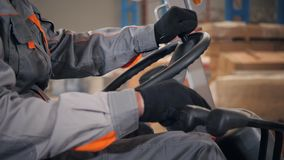 Close-upstuurwiel en hefbomen Mens die een vorkheftruck drijven door een pakhuis in een fabriek bestuurder in eenvormig en