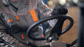 Close-upstuurwiel en hefbomen Mens die een vorkheftruck drijven door een pakhuis in een fabriek bestuurder in eenvormig en stock footage