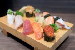 Close-upsushi en sashimi op houten plaat die op zwarte houten worden gemengd Royalty-vrije Stock Fotografie