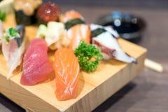 Close-upsushi en sashimi op houten plaat die op zwarte houten worden gemengd Stock Afbeeldingen