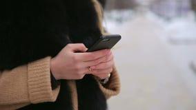 Close-uptelefoon in de handen van het meisje in de winter stock video