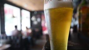 Close-upvideo met glas licht bier stock videobeelden