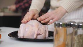 Close-upvoorbereiding van kip voor baksel Bestrooi het ruwe karkas met kruiden en zout stock videobeelden