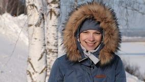 Close-upvrouw in blauw benedenjasje met frown van de bontkap van de zon en de glimlachen, in de winterpark stock video