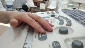Close-upvrouw de artsenhand drukt de scanner van de knopenultrasone klank in het kliniekziekenhuis Diagnostiek, echografie en gez stock video