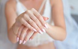 Close-upvrouw die haar handen met mooie manicure tonen De handen van de bruid met een aardige manicure stock foto